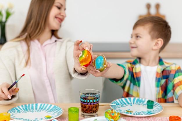 Смайлик мама и сын, показывая свои крашеные яйца