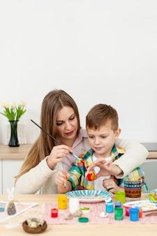 Мама помогает сыну красить яйца