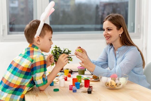 Вид сбоку мать и сын красят яйца
