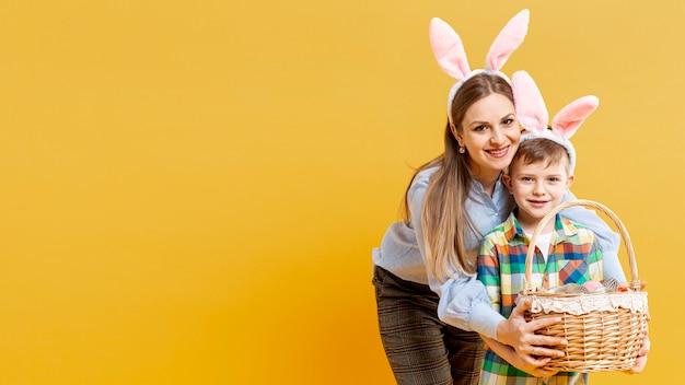 コピースペースの母と塗装卵のバスケットを持つ息子