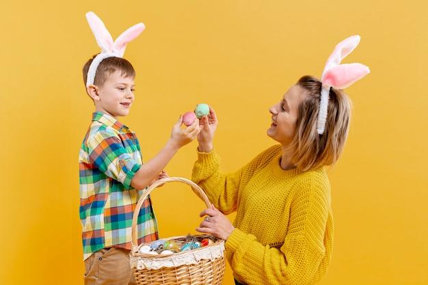 Высокий угол мать и сын с крашеными яйцами