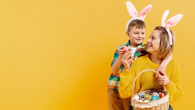 コピースペースのお母さんと塗装卵がいっぱい入ったかごを持つ息子