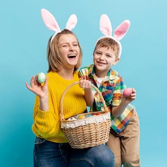 Счастливая мать и сын с крашеными яйцами в корзине