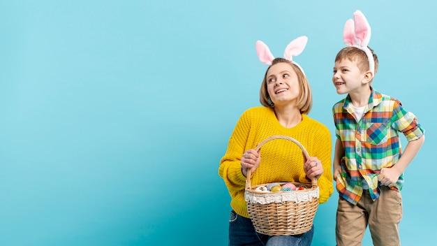 イースターのために準備塗装卵を保持している息子とコピースペースママ