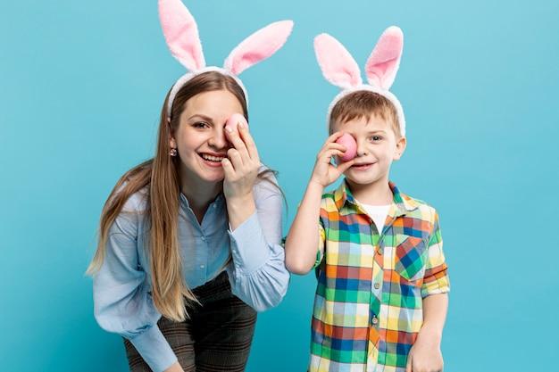 Мать и сын с кроличьими ушами закрывают глаза крашеными яйцами