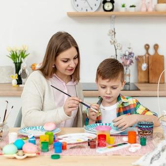 Высокий угол мама помогает сыну красить яйца