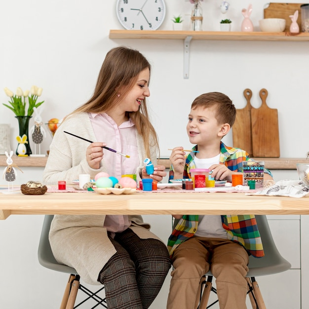 Мать и сын, вид спереди, рисуют яйца на пасху