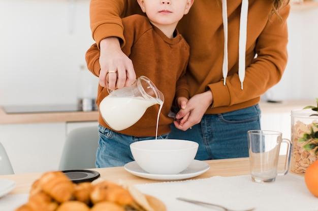 Крупным планом мать и сын наливает молоко