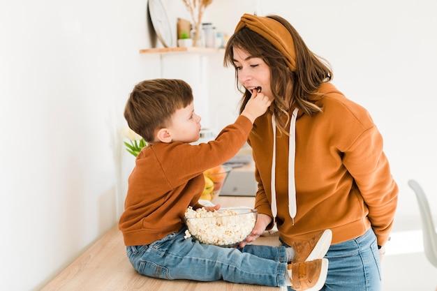 彼のお母さんに餌をやる少年