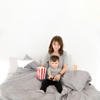 Высокий угол мать и сын едят попкорн