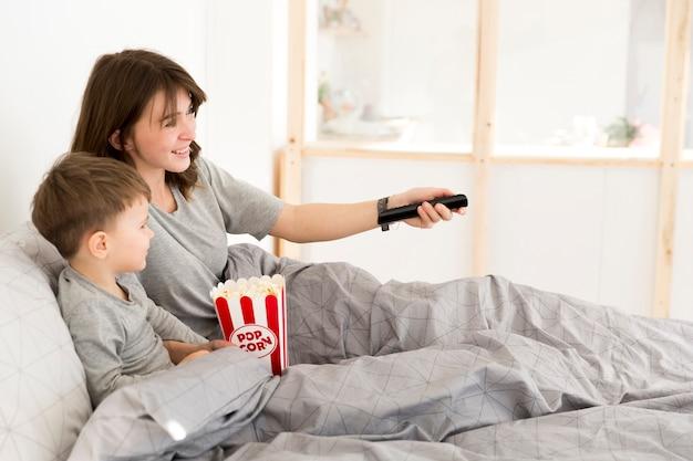 母と息子はベッドでテレビを見て