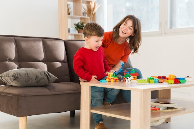 Мать-смайлик наблюдает за тем, как сын играет