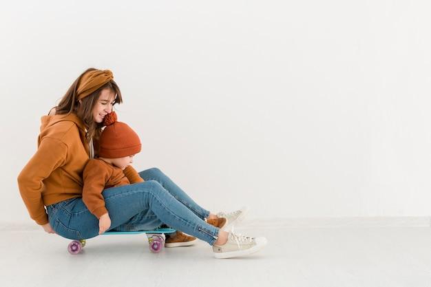 Вид сбоку мама с маленьким мальчиком на скейтборде