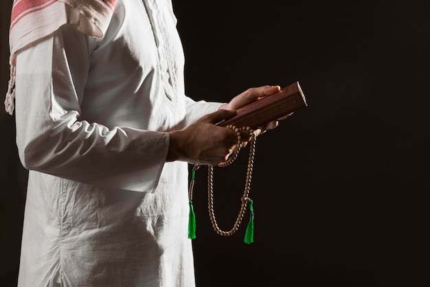 Человек в традиционной арабской одежде держит коран