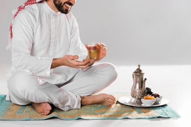 座っているとアラビア語のお茶のカップを保持している男