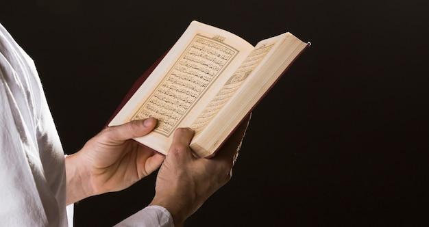 手で開いているコーランを持つ男