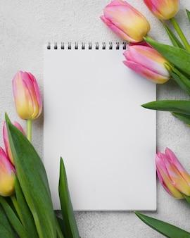 ノートブックの横にあるピンクのチューリップ