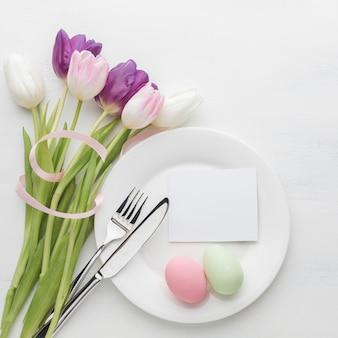 Вид сверху тарелка с пасхальными яйцами и тюльпаны со столовыми приборами