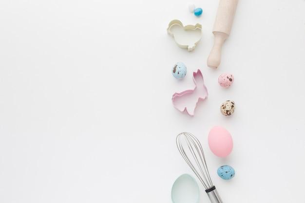Вид сверху пасхальных яиц с кухонной утварью и фигурками зайчиков
