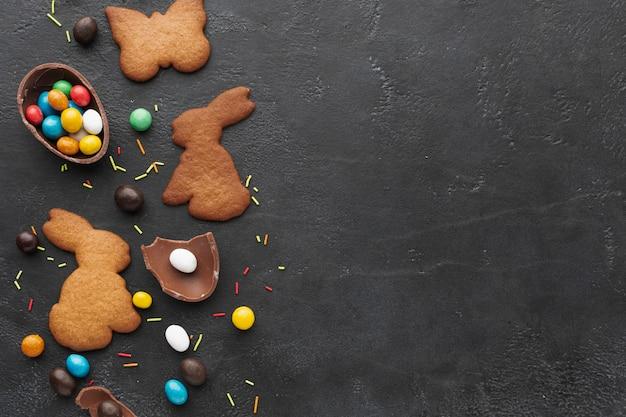 コピースペースとお菓子でいっぱいのチョコレートの卵とイースターのバニーの形をしたクッキーのフラットレイアウト