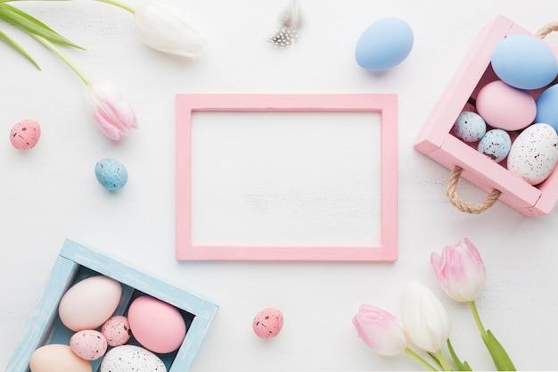 Взгляд сверху милых коробок с красочными пасхальными яйцами и рамкой