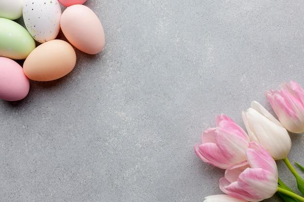 Вид сверху на красочные пасхальные яйца и красивые тюльпаны