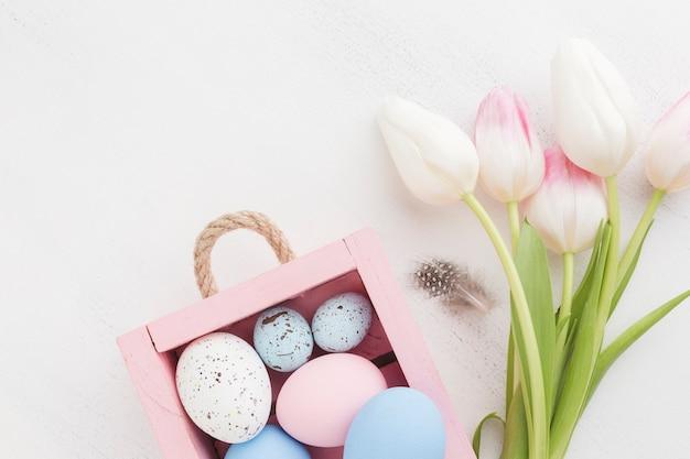Вид сверху разноцветных пасхальных яиц с милыми тюльпанами