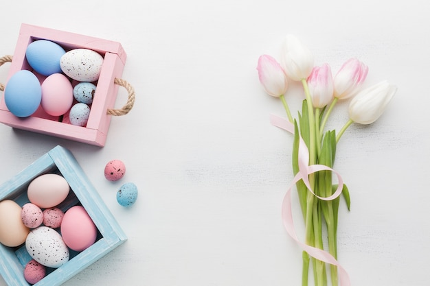 Вид сверху разноцветных пасхальных яиц с красивыми тюльпанами