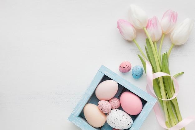 Вид сверху красивые тюльпаны с красочными пасхальными яйцами