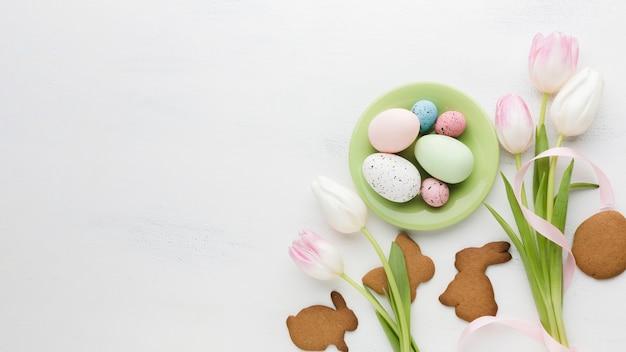 Вид сверху тюльпанов с разноцветными пасхальными яйцами