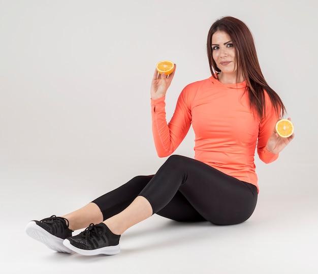 Взгляд со стороны женщины представляя в одежде спортзала с апельсином