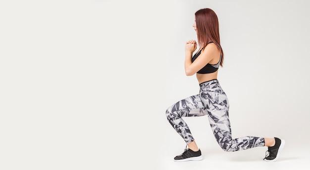Взгляд со стороны атлетической женщины делая выпады