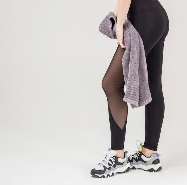 タオルを保持しながらポーズをとって運動女性の足の側面図