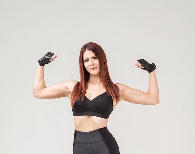 彼女の上腕二頭筋を示す運動女性の正面図