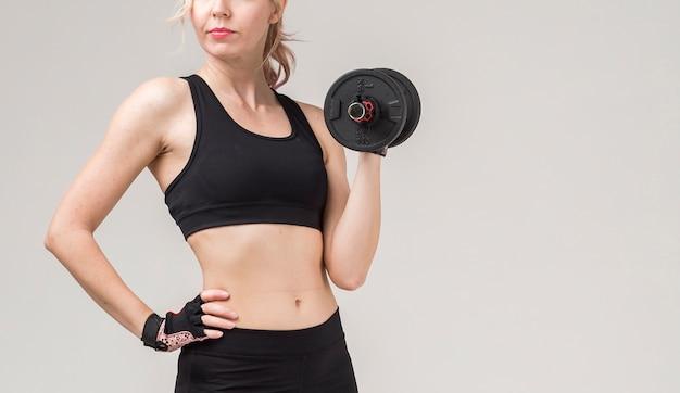 スポーティな女性の持ち上がる重量の正面図
