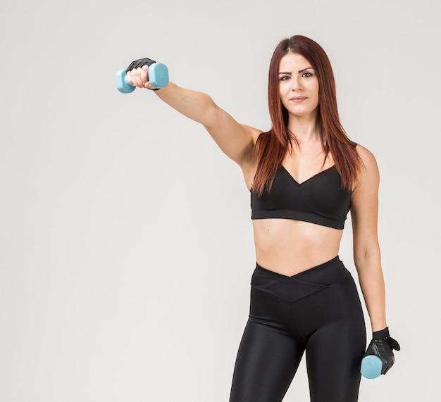 重みで運動するスポーティな女性の正面図