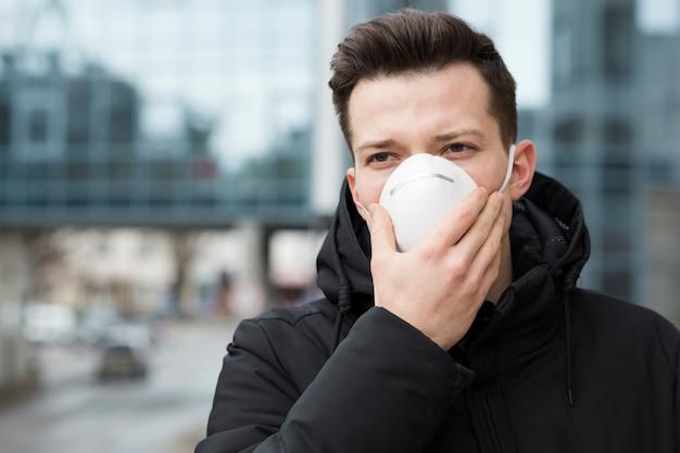 Мужчина держит медицинскую маску над ртом