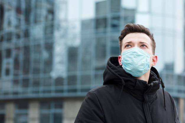 コピースペースが付いている都市でポーズをとって医療マスクを持つ男