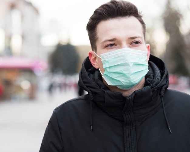 Вид спереди человека в городе носить медицинскую маску