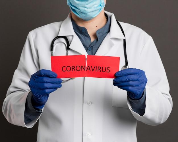 コロナウイルスで破れた紙を保持している手術用手袋を持つ医師