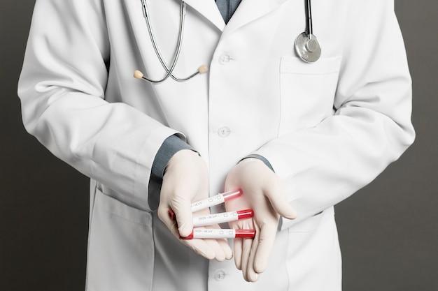 Вид спереди доктора с хирургическими перчатками, держащими вакутейнеры