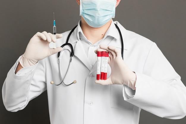 注射器とバキュテナーを保持している医療マスクを持つ医師