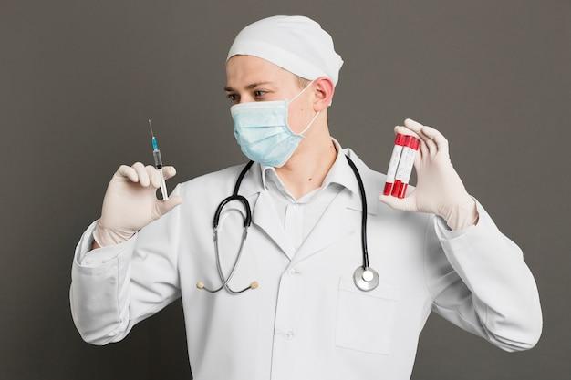 注射器とバキュテナーを保持している医者の正面図