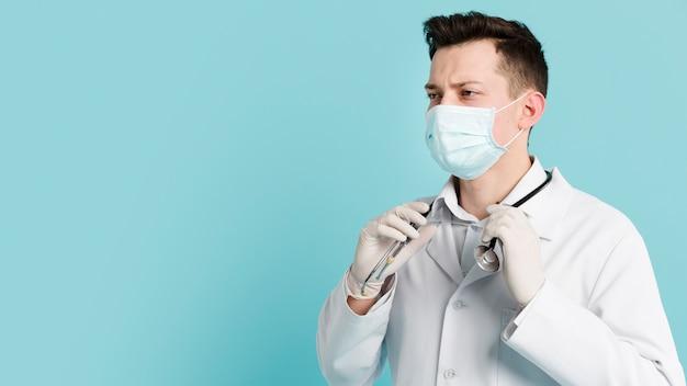 彼の聴診器を保持している医療マスクを持つ医師