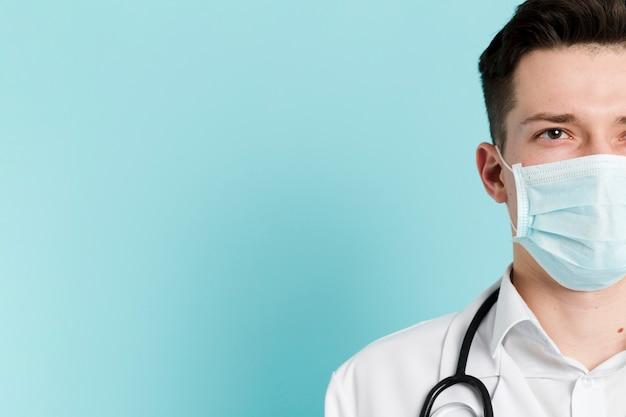 医療用マスクを身に着けている医師の顔の半分の正面図