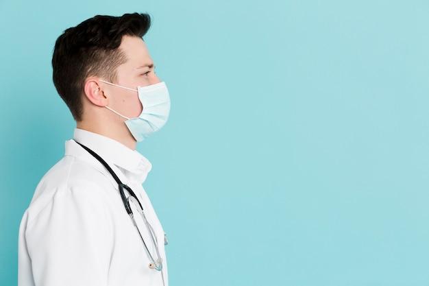 医療マスクと聴診器を持つ医師の側面図