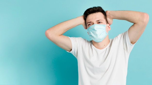 Человек позирует во время ношения медицинской маски с копией пространства