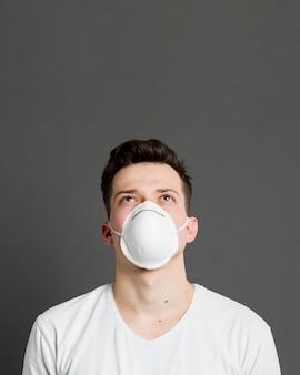 Вид спереди человека, носящего медицинскую маску с копией пространства