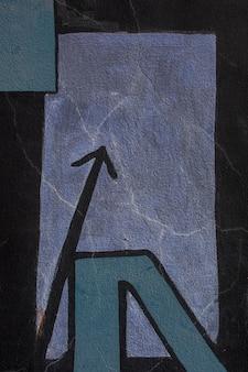 落書きの壁に黒塗りの矢印