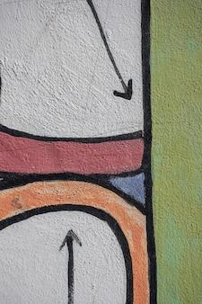 カラフルな落書きの壁に黒塗りの矢印